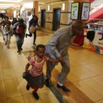 People with children run for safety as armed police hunt gunmen who went on a shooting spree at Westgate shopping centre in Nairobi