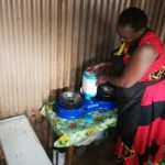Mary Omweno fixing ethanol fuel canister into a cooker ready to warm food for her customers (1)